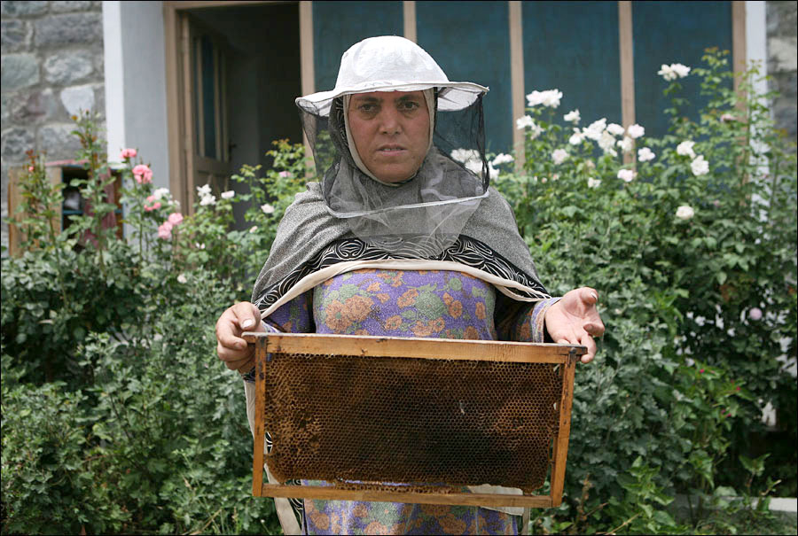 An entrepreneur/honey farmer poses with her bee hive in front of her house in Gilgit.